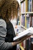 de jonge tiener kiest een boek in de opslag Stock Afbeelding