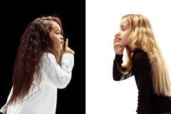 De jonge tienermeisjes die een geheim achter haar fluisteren overhandigen roze achtergrond stock foto's