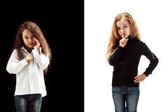 De jonge tienermeisjes die een geheim achter haar fluisteren overhandigen roze achtergrond royalty-vrije stock fotografie