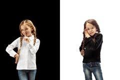 De jonge tienermeisjes die een geheim achter haar fluisteren overhandigen roze achtergrond royalty-vrije stock afbeelding
