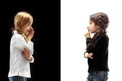 De jonge tienermeisjes die een geheim achter haar fluisteren overhandigen roze achtergrond royalty-vrije stock afbeeldingen