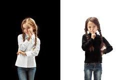 De jonge tienermeisjes die een geheim achter haar fluisteren overhandigen roze achtergrond stock afbeelding