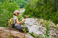 De jonge toerist met rugzak zit en glimlachend genietend van mooi Th stock foto