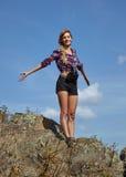 De jonge toerist van de blondevrouw in overhemd en borrels op een klip op B royalty-vrije stock foto's