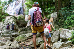 De jonge toeristen bewegen zich over de kreek op de rotsen in de wildernis Royalty-vrije Stock Foto's
