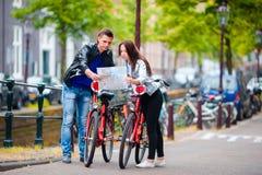 De jonge toeristen koppelen het bekijken kaart aan fietsen in Europese stad stock afbeeldingen