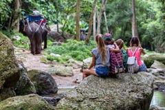 De jonge toeristen rusten op de rotsen in de wildernis Stock Afbeelding
