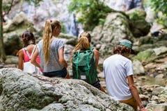 De jonge toeristen rusten op de rotsen in de wildernis Stock Afbeeldingen