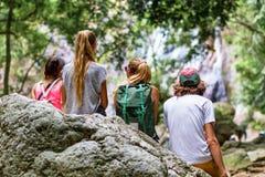 De jonge toeristen rusten op de rotsen in de wildernis Stock Foto
