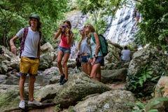 De jonge toeristen rusten op de rotsen in de wildernis Stock Fotografie