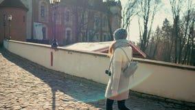 De jonge toeristenvrouw loopt dichtbij middeleeuws kasteel en neemt foto door camera stock video