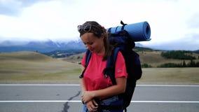 De jonge toeristenvrouw met een rugzak en zonnebril lift op een bergweg Het meisje is het wrijven zijn handen van stock footage