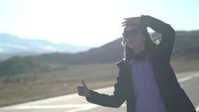 De jonge toeristenvrouw met een rugzak en zonnebril probeert om het telefoonsignaal op een bergweg te vangen Er zijn stock video