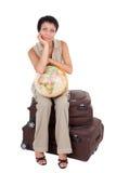 De jonge toeristenvrouw zit op bruine koffer Royalty-vrije Stock Afbeeldingen