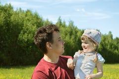 De jonge vader bekijkt gelukkig weinig dochter stock foto's