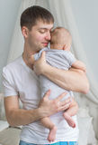De jonge vader houdt thuis op handen haar weinig baby (achtermening) stock foto's