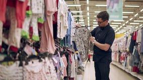 De jonge vader kiest kleding in een kinderenafdeling in opslag stock footage