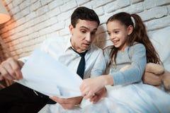 De jonge vader vertelt zijn dochter over zijn werk De zakenman toont weinig dochter dan hij  stock afbeeldingen