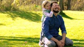 De jonge vaderzitting op groen gras en glimlachend meisje lanceert aan hem en zet haar handen aan zijn ogen stock videobeelden