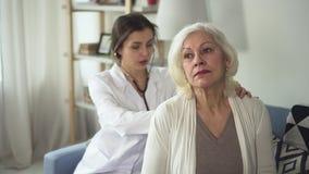 De jonge vakman luistert aan volwassen geduldige gebruikende stethoscoop op vrouw terug door langzame moties stock videobeelden