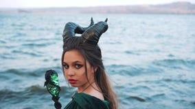 De jonge vampierjacht, meisje met lang haar in smaragdgroene kleding met magisch personeel draait haar gezicht aan camera, dame m stock footage