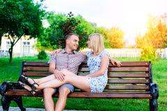 De jonge van de paarman en vrouw zitting op een bank die in parklint koesteren, verklaring van liefde, verzacht omhelzing, het co stock fotografie