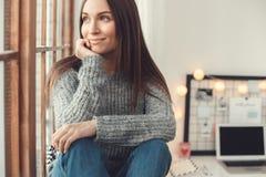 De jonge van het het bureauconcept van het vrouwen freelancer binnen huis zitting van de de winteratmosfeer op venstervensterbank stock foto's