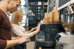 De jonge van de paarman en vrouw eigenaars kleine bedrijfskoffie winkelt, werkend dichtbij koffiemachines, makend dranken royalty-vrije stock afbeelding