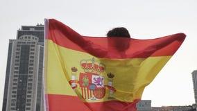 De jonge ventilator die van het meisjesvoetbal een vlag van Spanje in de stad houden, kampioenschapsconcept 50 fps stock footage