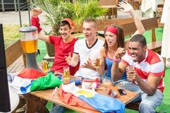 De jonge ventilators die van de voetbalverdediger met bier het letten op sport toejuichen Stock Foto's