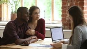 De jonge vergadering van de multi-etnisch paar plannende hypotheek met makelaar in onroerend goed stock video