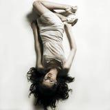 De jonge verleidelijke vrouw legt op witte bedsheet Stock Fotografie