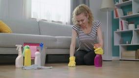 De jonge vermoeide vrouw veegt de vloer met inspanning af stock video