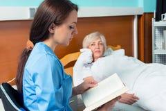 De jonge verpleegster in eenvormig leest een boek en zittend patien dichtbij Stock Foto's