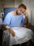 De jonge verwonde mens in de zitting van de het ziekenhuisruimte alleen in pijn maakte zich voor zijn gezondheidsvoorschrift onge Stock Afbeeldingen