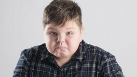 De jonge vette jongen toont woede, agressie en haat stock footage