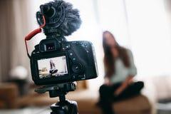 De jonge video van de vrouwenopname voor haar vlog die camera met micro met behulp van stock fotografie
