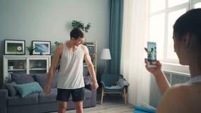 De jonge video van de vrouwenopname van knappe mannelijke bodybuilder die smartphonecamera met behulp van stock video