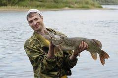 De jonge visser houdt en bekijkt de grote snoeken Royalty-vrije Stock Afbeelding