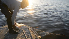 De jonge visser verwijdert de vissen uit de netten en werpt het aan de boot stock videobeelden