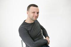 De jonge volwassen Europese mens zit op stoel Royalty-vrije Stock Afbeeldingen