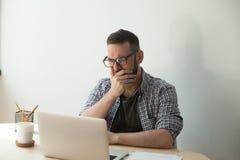 De jonge volwassen mens die vreselijk nieuwsartikel in zijn laptop lezen verwerkt gegevens Royalty-vrije Stock Foto
