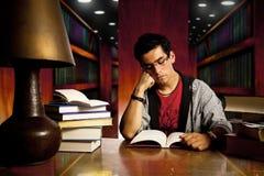 De jonge volwassen student leest boek bij bibliotheek Royalty-vrije Stock Foto