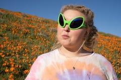 De jonge volwassen vrouw die vreemde zonnebril en een t-shirt van de bandkleurstof bevindt dragen zich op een gebied van papavers stock fotografie
