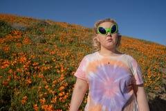 De jonge volwassen vrouw die vreemde zonnebril en een t-shirt van de bandkleurstof bevindt dragen zich op een gebied van papavers stock afbeeldingen