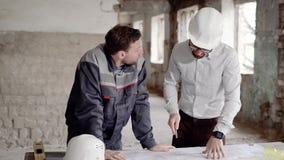 De jonge voorman gekleed in eenvormig bevindt zich op het bouwterrein en bekijkt bouwblauwdruk De arbeider is stock video