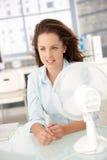 De jonge voorzijde die van de vrouwenzitting van ventilator koelt Stock Fotografie