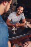 De jonge vrienden die bij een koffie zitten dienen het hebben van dranken in stock fotografie