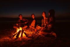 De jonge vrienden hebben picknick met vuur op het strand stock afbeelding