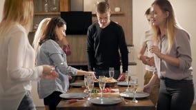 De jonge vriendenmensen dienen lijst, zettend maaltijd en vaatwerk voor vieringsdiner in huis stock videobeelden